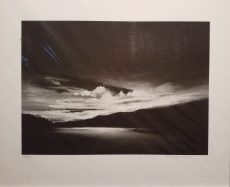 Black and white print of riverbend. Most light is at center of horizon which illuminates scattered clouds just above the river and shimmers light off the river to show us where it flows.