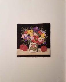 White vase with neat pattern holds dazzling bouquet of flowers and sits atop light table with three red apples. Black background.