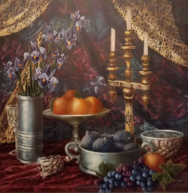 Velvet table is set lavishly with bowls of oranges and figs and bunches of grapes sprawl across the table in front. Three candles and a vase also line the table and a golden and red curtain drape and fold in the background.